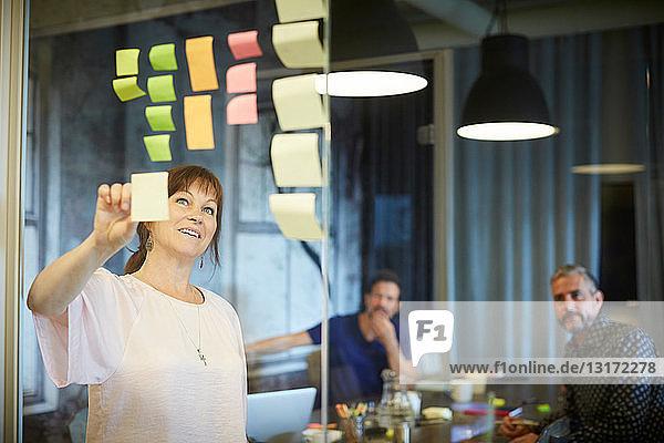 Kreative Geschäftsleute beim Brainstorming von Ideen über Haftnotizen im Sitzungssaal