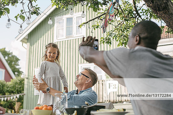 Mann fotografiert Tochter  die während einer Gartenparty am Tisch neben einem älteren Mann steht