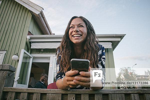 Glückliche Frau im mittleren Erwachsenenalter benutzt Mobiltelefon  während sie sich auf der Veranda an ein Geländer lehnt