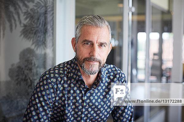 Porträt eines reifen Geschäftsmannes  der in einem kreativen Büro sitzt