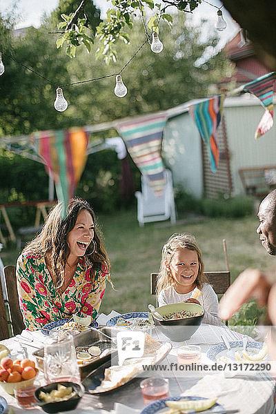 Glückliche Familie beim Mittagessen am Tisch im Garten während der Gartenparty