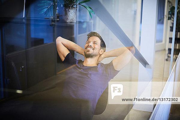 Kreativer Geschäftsmann entspannt sich auf einem Stuhl mit Blick durch Glas im Büro