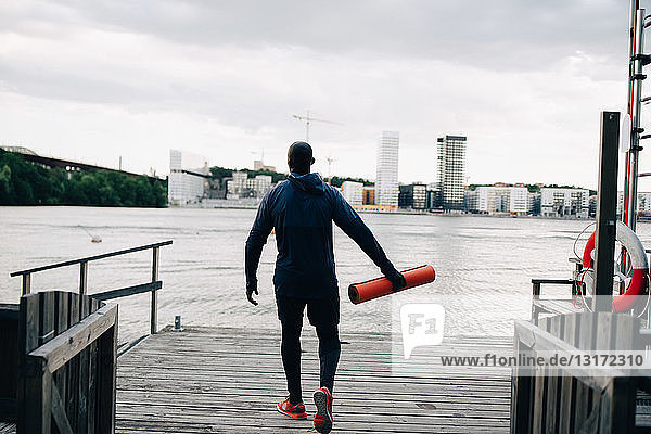 Rear view of male athlete holding yoga mat while walking on pier over sea in city