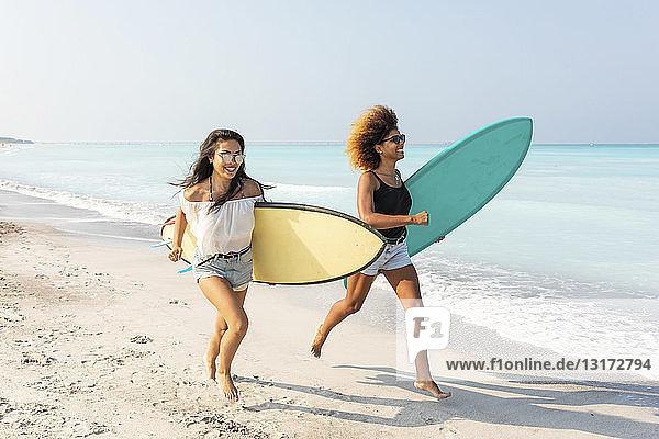 Freundinnen laufen am Strand und tragen Surfbretter
