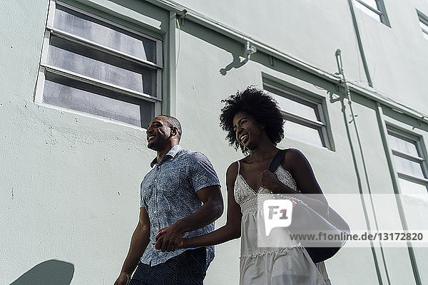 Smiling young couple walking along building