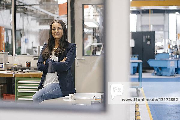 Selbstbewusste Frau sitzt in einem High-Tech-Unternehmen  steht mit verschränkten Armen in einer Fabrikhalle