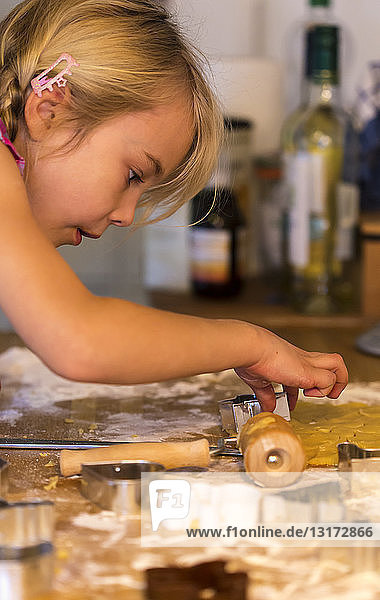 Little girl cutting out cookies with cookie cutter at Christmas time
