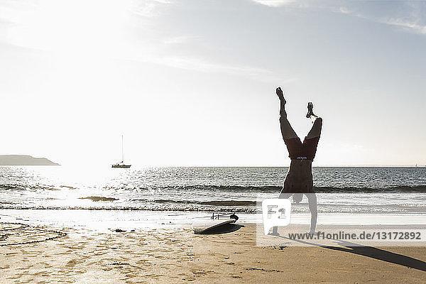 Frankreich  Bretagne  junger Mann macht einen Handstand am Strand neben dem Surfbrett