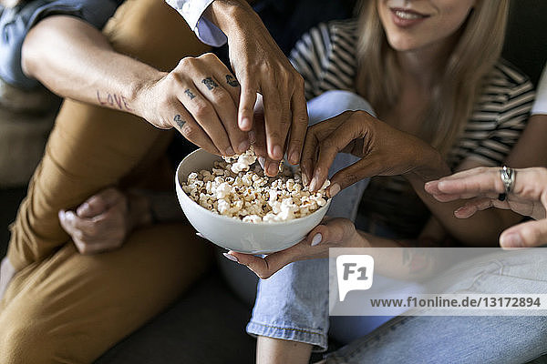 Close-up of friends sitting on couch sharing a bowl of popcorn