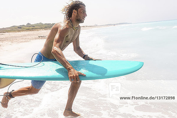 Junger Mann läuft mit seinem Surfbrett ins Meer