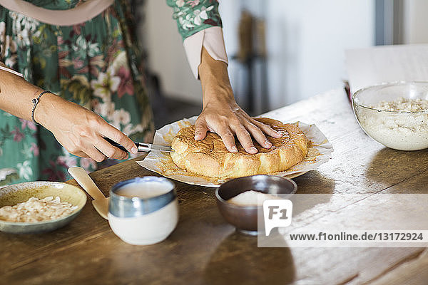 Young woman cutting home-baked cake  partial view