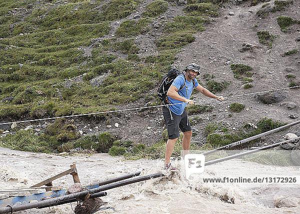 Russia  Caucasus  Mountaineer crossing river in Upper Baksan Valley