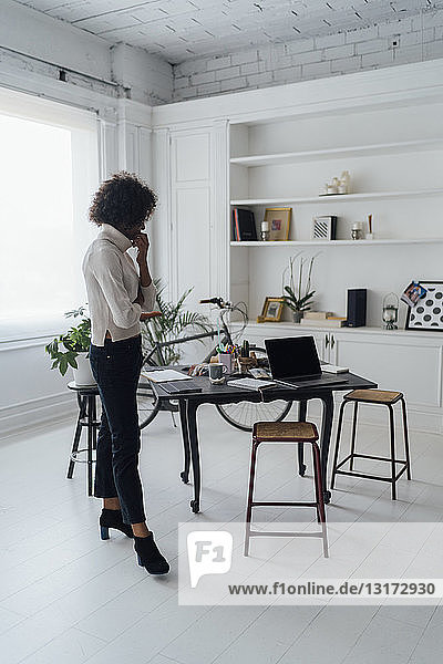 Freelancer standing in her home office  thinking