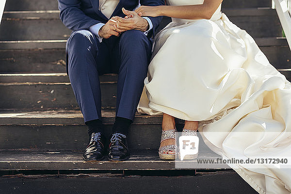 Bridal couple sitting on stairs outdoors  partial view