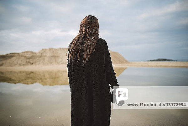 Back view of photographer dressed in black standing on the beach