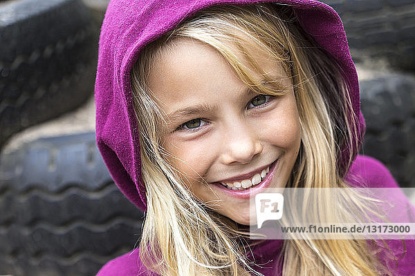 Portrait of smiling blond girl wearing pink hooded jacket