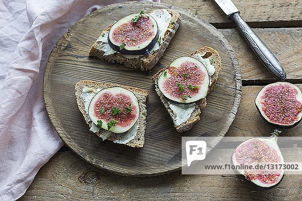 Gebutterte Brotscheiben mit geschnittenen Feigen auf Holzplatte