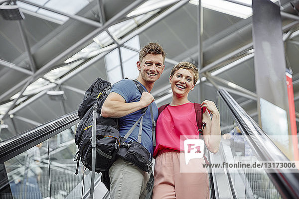 Glückliches Paar auf der Rolltreppe am Flughafen