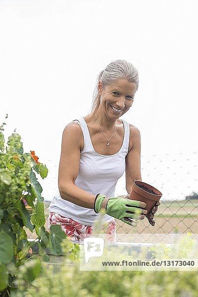 Porträt einer lächelnden Frau  die am Hochbeet gärtnert