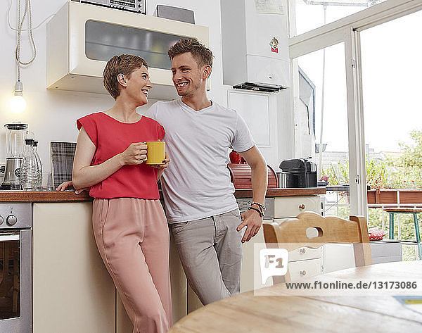 Happy couple at home having a coffee break in kitchen