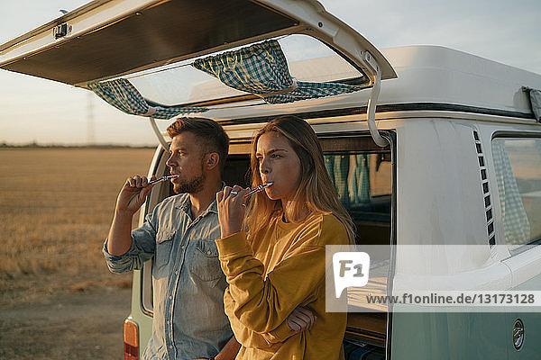 Ehepaar beim Zähneputzen am Wohnmobil in ländlicher Landschaft bei Sonnenuntergang
