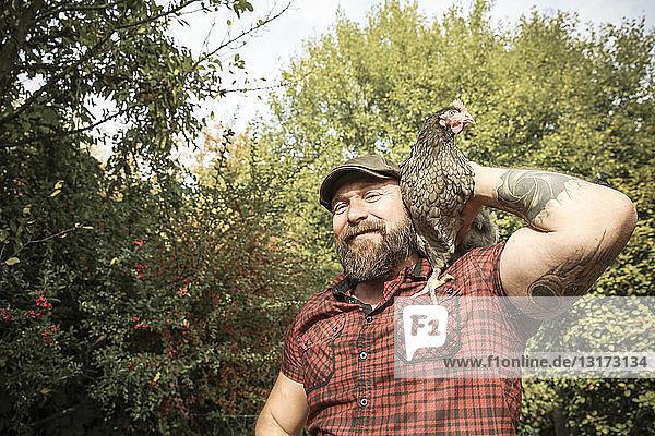 Man in his own garden  man with free range chicken on his shoulder