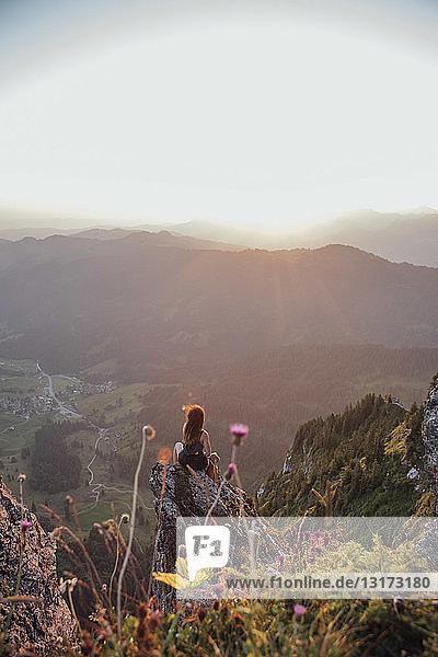 Schweiz  Grosse Mythen  junge Frau auf einer Wanderung  die bei Sonnenaufgang auf einem Felsen sitzt