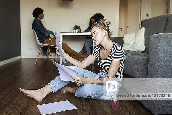 Junge Frau sitzt auf dem Boden mit Papieren und Freunden im Hintergrund