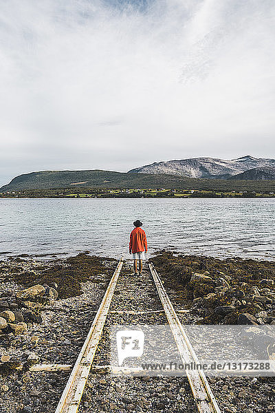Northern Norway  Man standing alone at fjord  looking at view