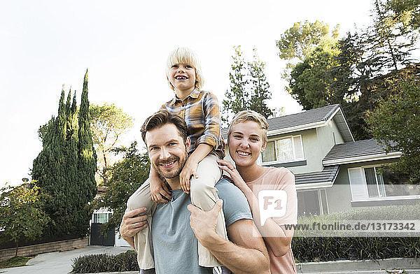 Porträt von lächelnden Eltern mit Sohn vor ihrem Haus