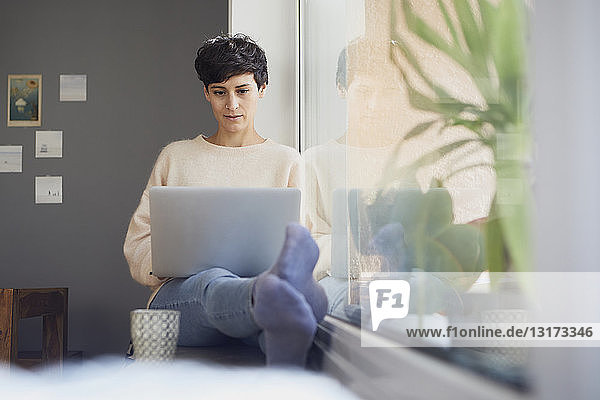 Woman at home sitting at the window using laptop