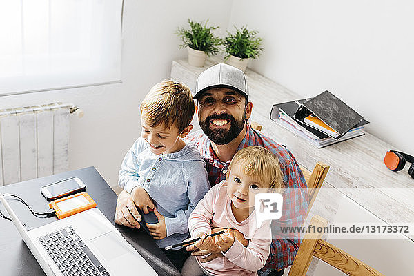 Father working at home  using laptop with his children on his lap