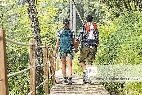 Italien  Massa  Rückansicht eines jungen Paares beim Wandern und Spazierengehen auf einer Strandpromenade in den Alpi Apuane