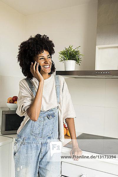 Glückliche Frau am Handy in der heimischen Küche