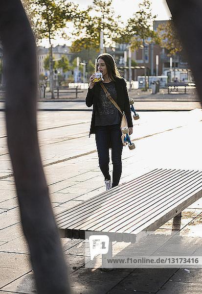 Junge Frau mit Longboard bei einem Imbiss in der Stadt