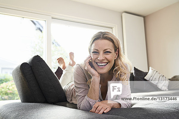 Porträt einer lachenden Frau  die zu Hause auf dem Sofa liegt