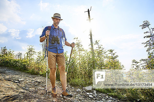 Man walking carefully with hiking poles on trail