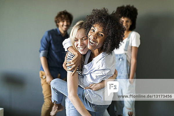 Two happy women hugging with friends in background