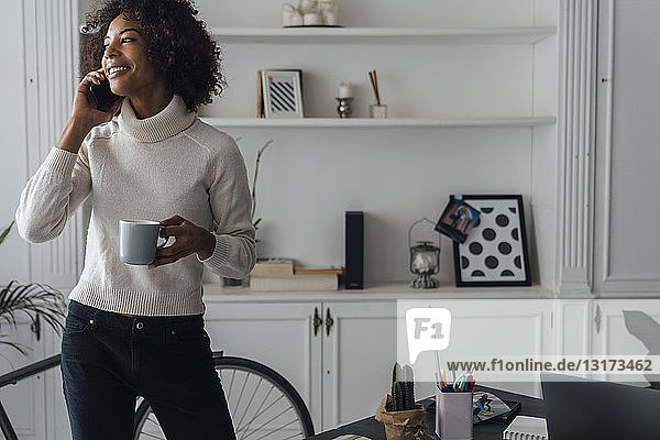 Mid adult freelancer standing in her home office  drinking coffee  talking on the phone