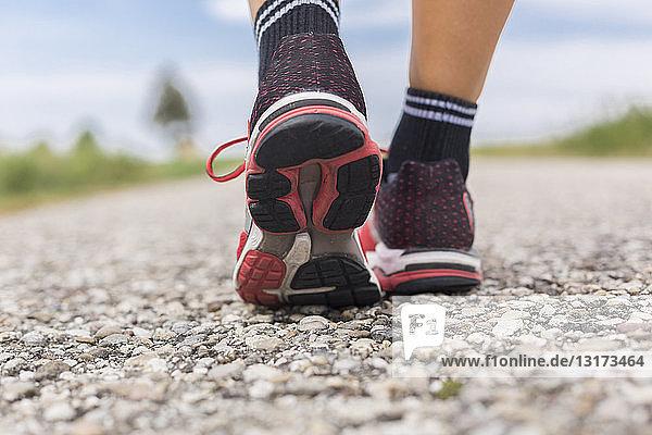Füße einer sportlichen Frau auf dem Feldweg im Sommer