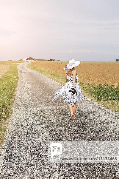 Rückansicht einer reifen Frau  die im Sommer auf einem abgelegenen Feldweg geht