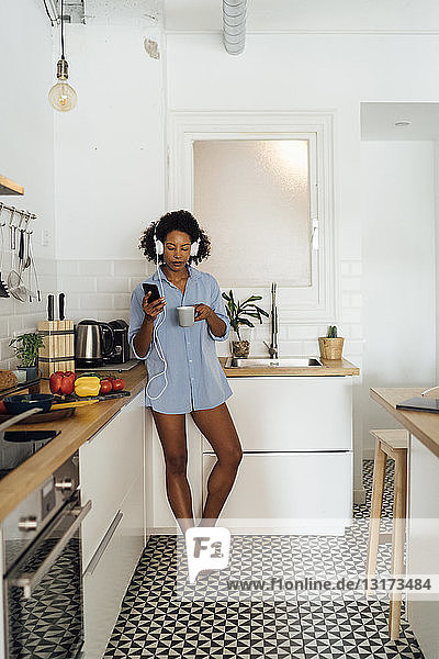 Woman with headphones  using smartphone and drinking coffee for breakfast in her kitchen