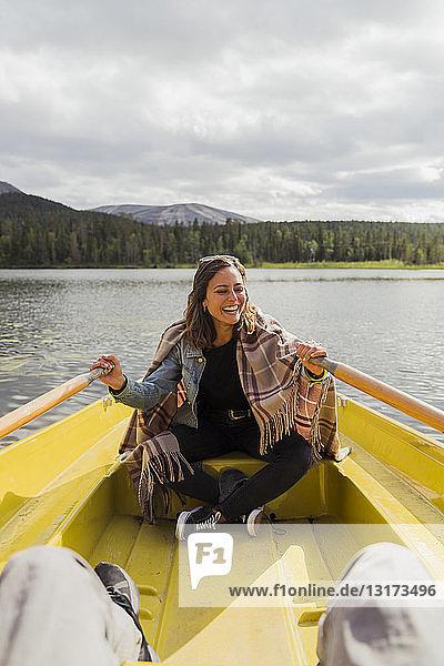 Finnland  Lappland  lachende Frau mit einer Decke in einem Ruderboot auf einem See