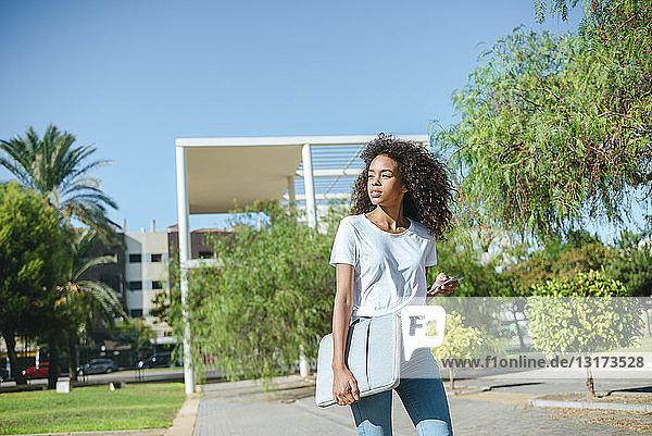 Porträt einer jungen Frau mit Handy und Laptoptasche  die die Straße entlang geht und auf ihr Handy schaut