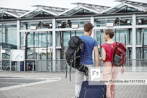 Rückansicht eines Paares zu Fuß vor dem Flughafen