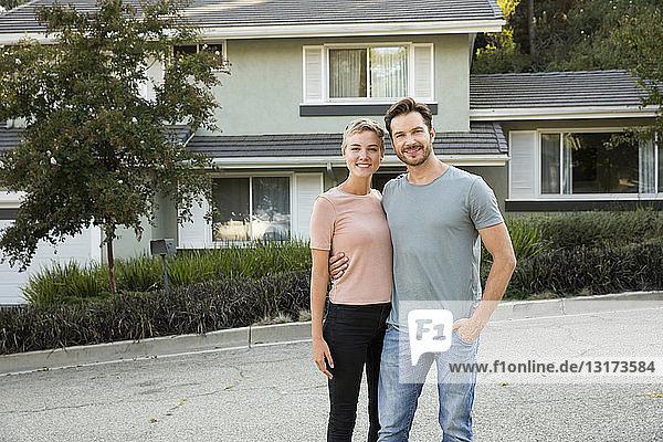 Porträt eines lächelnden Paares vor ihrem Haus