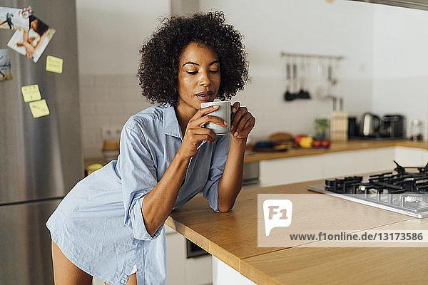 Frau steht in ihrer Küche und trinkt ihren Morgenkaffee