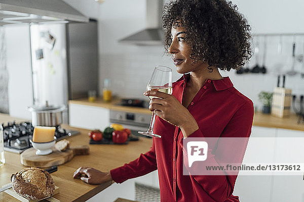 Woman standing in kitchen  drinking a glass of white wine