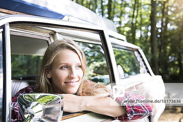 Smiling young woman in car in forest