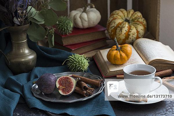 Herbstliches Stilleben mit Feigen  Zimtstangen  Büchern und einer Tasse Tee